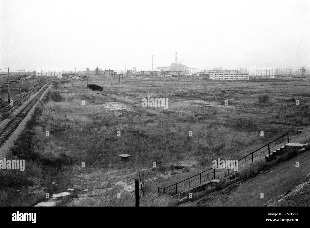 Radiated landscape in the 30 km restricted zone, in the background the Chernobyl disaster reactor in the concrete sarcophagus. - Stock Image