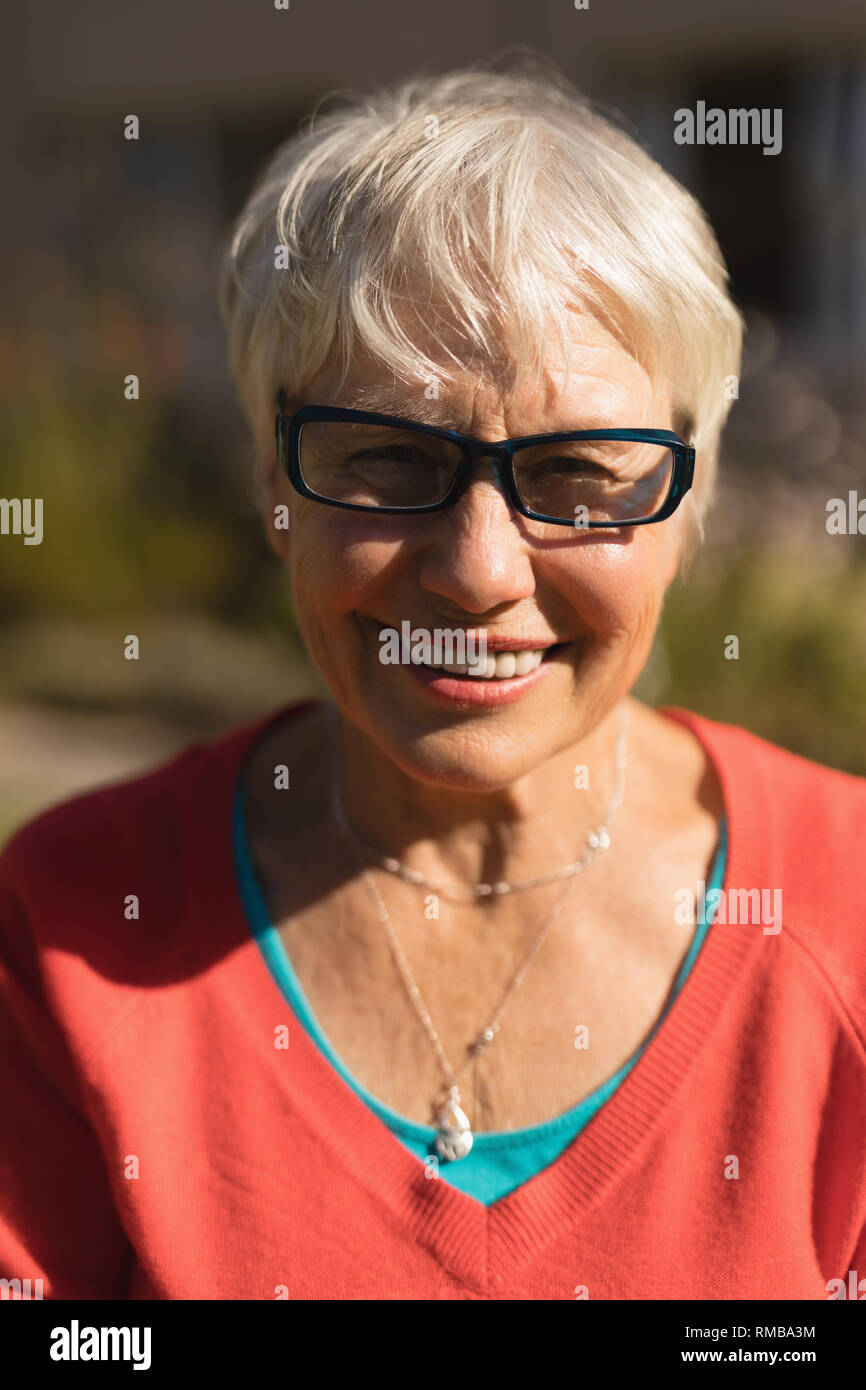 Senior woman in spectacle smiling in the park - Stock Image