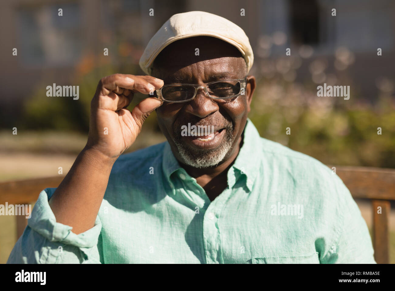 Senior man in spectacle smiling in the park - Stock Image