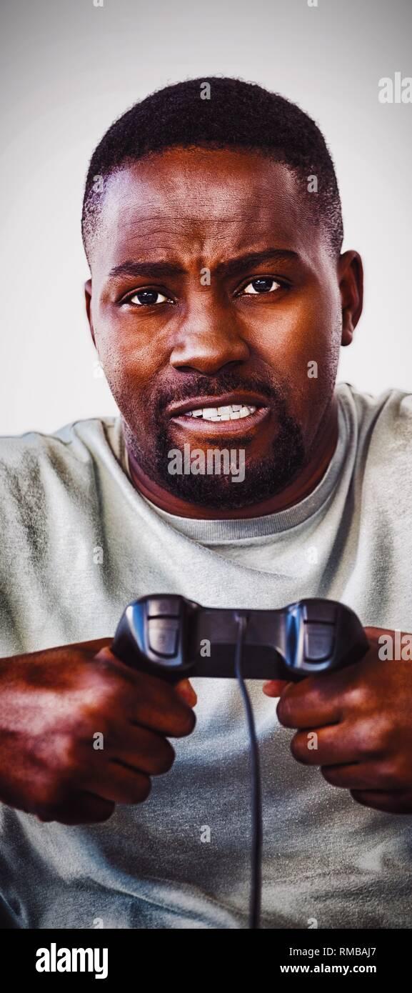 Frustrated man holding joystick against white background - Stock Image