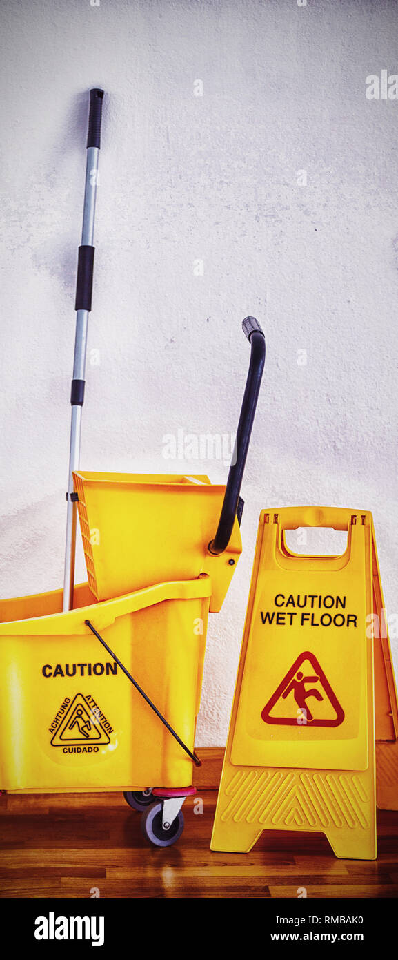 Yellow sign board with mop bucket on floor against wall - Stock Image