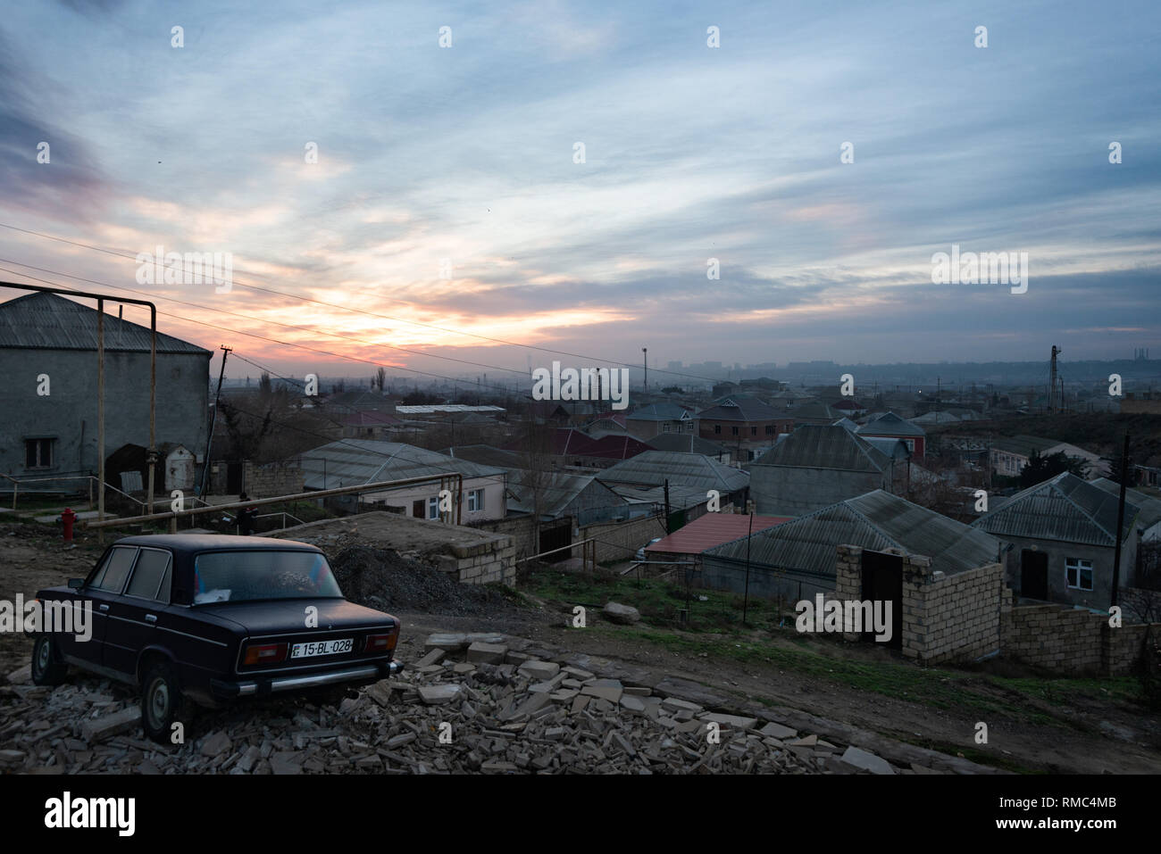 Sunrise over the outskirts of Baku with an old Lada in the foreground, Azerbaijan taken in January 2019 - Stock Image