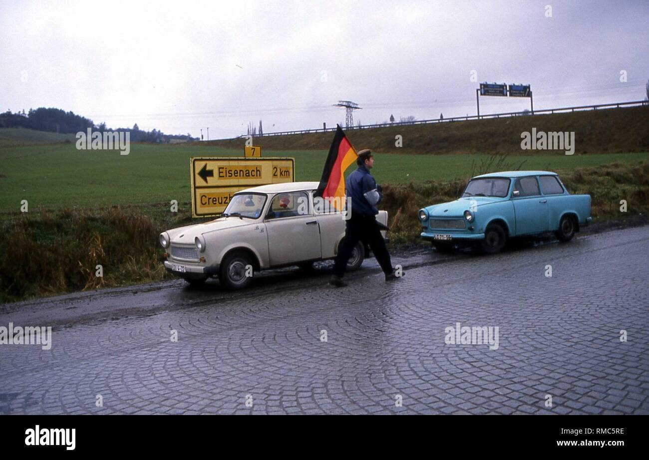 A man with a Germany flag, with two Trabants in the background in Eisenach. - Stock Image