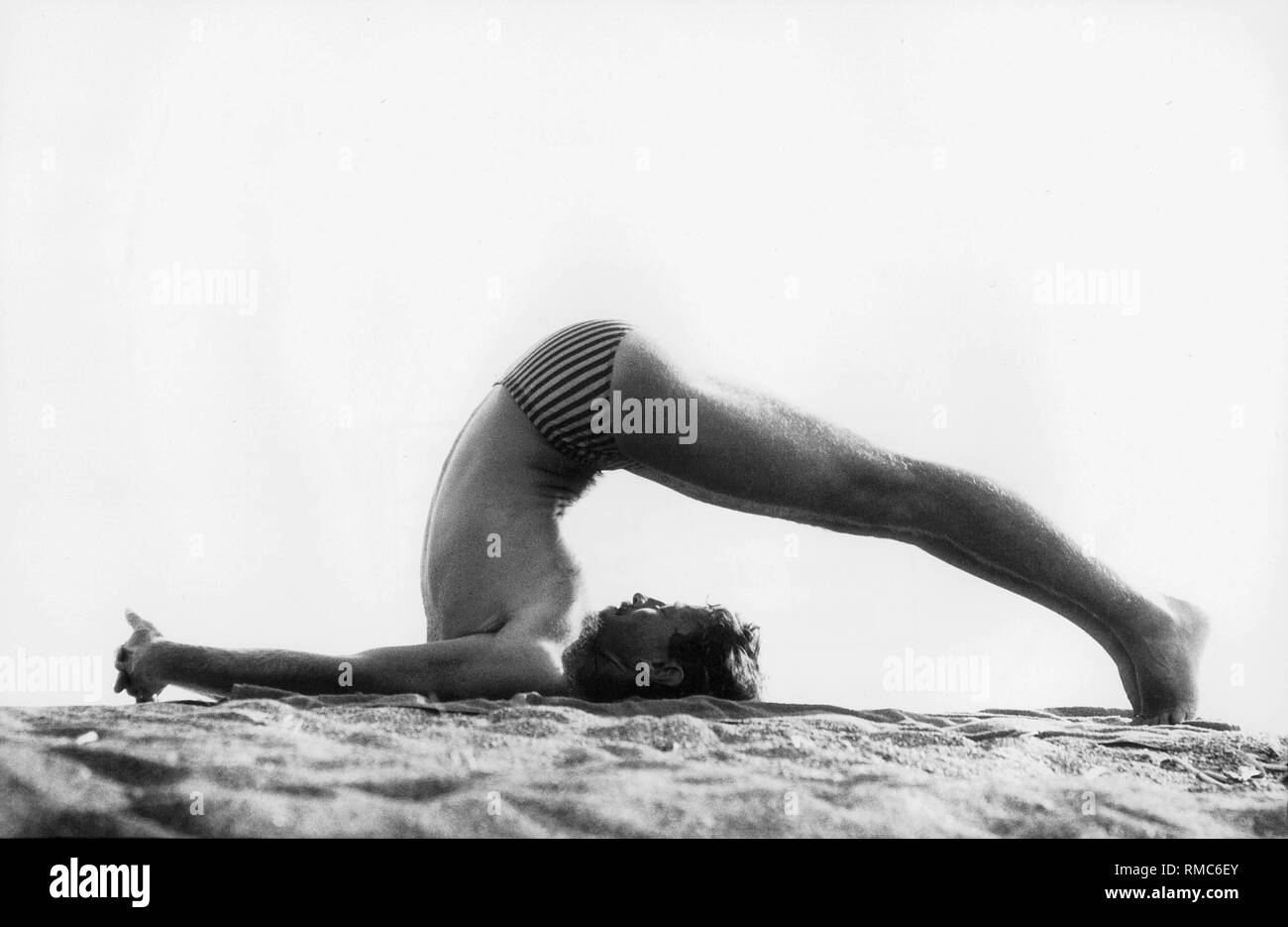 Yoga trains each part of the body, stretches and strengthens muscles and joints, the spine and the entire skeleton. Physical and mental tensions are released and amazing energy reserves are activated. The soul travels inwards and harmony of physical and mental strength is reached. In the picture, the Plow Pose. - Stock Image
