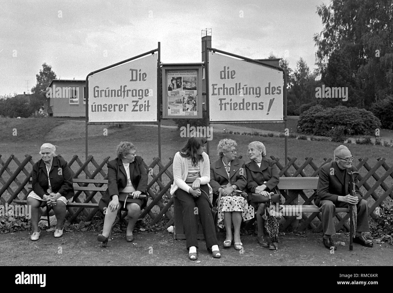 Women and a man sit and talk on two benches in a city in the GDR, behind them are two socialist propaganda posters with the inscription 'The basic question of our time - the preservation of peace'. - Stock Image