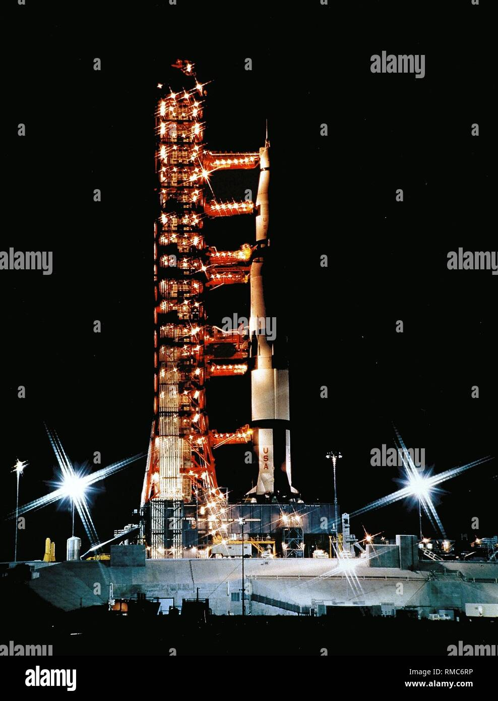 Evening preparations for launching an Apollo program at the Kennedy Space Center. The propulsion rocket of the Apollo program, the Saturn V, and the spacecraft are brought into position at the launch pad. Undated photo, probably from the 1980s. - Stock Image