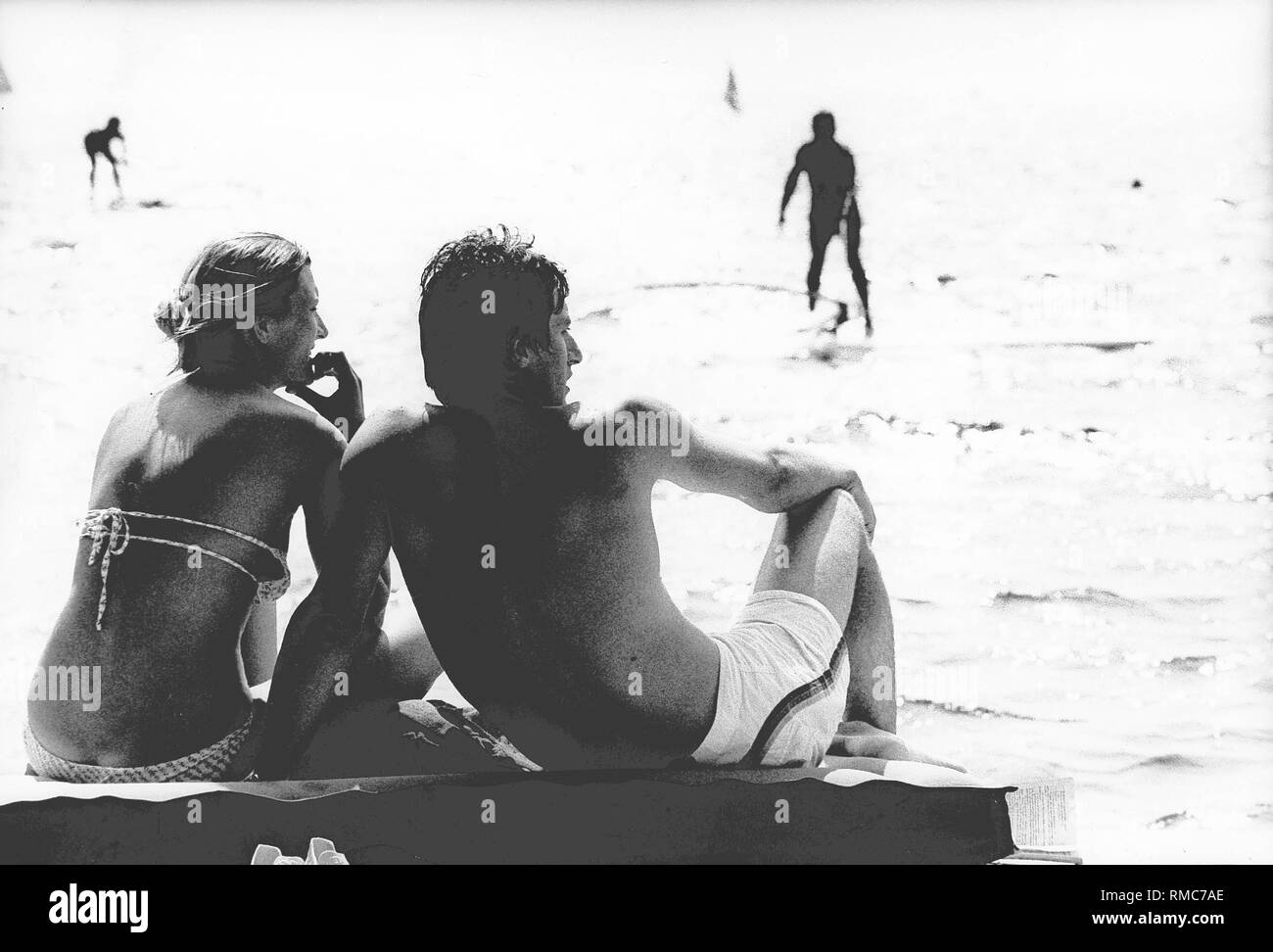 A man in swimming trunks and a woman in bikini are looking interested at surfers on the lake. - Stock Image