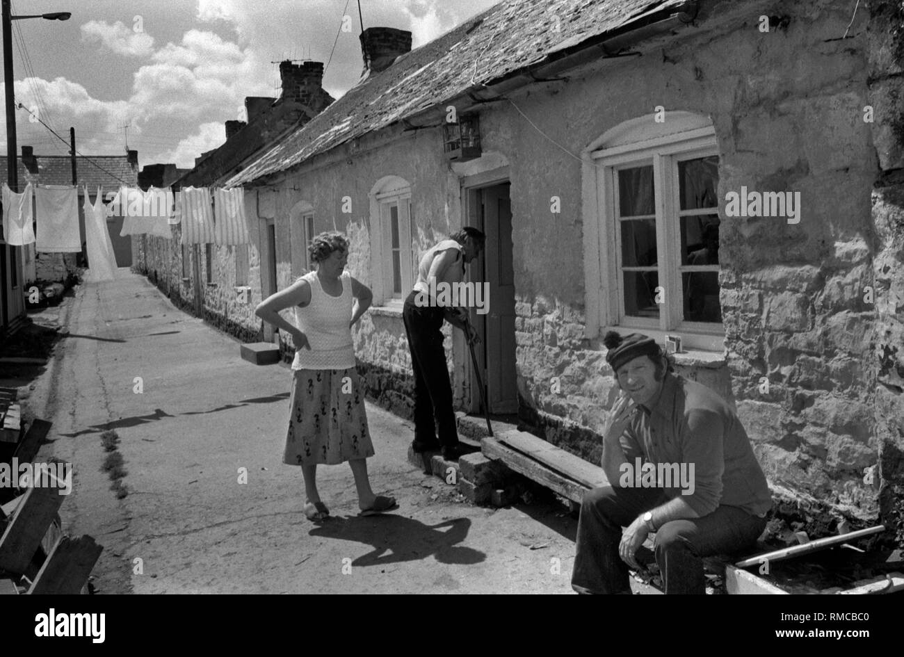 1970s  fisherman sitting outside the fisherman's cottages  Limerick, in County Limerick, Eire.  West Coast of Southern Ireland 70s HOMER SYKES - Stock Image