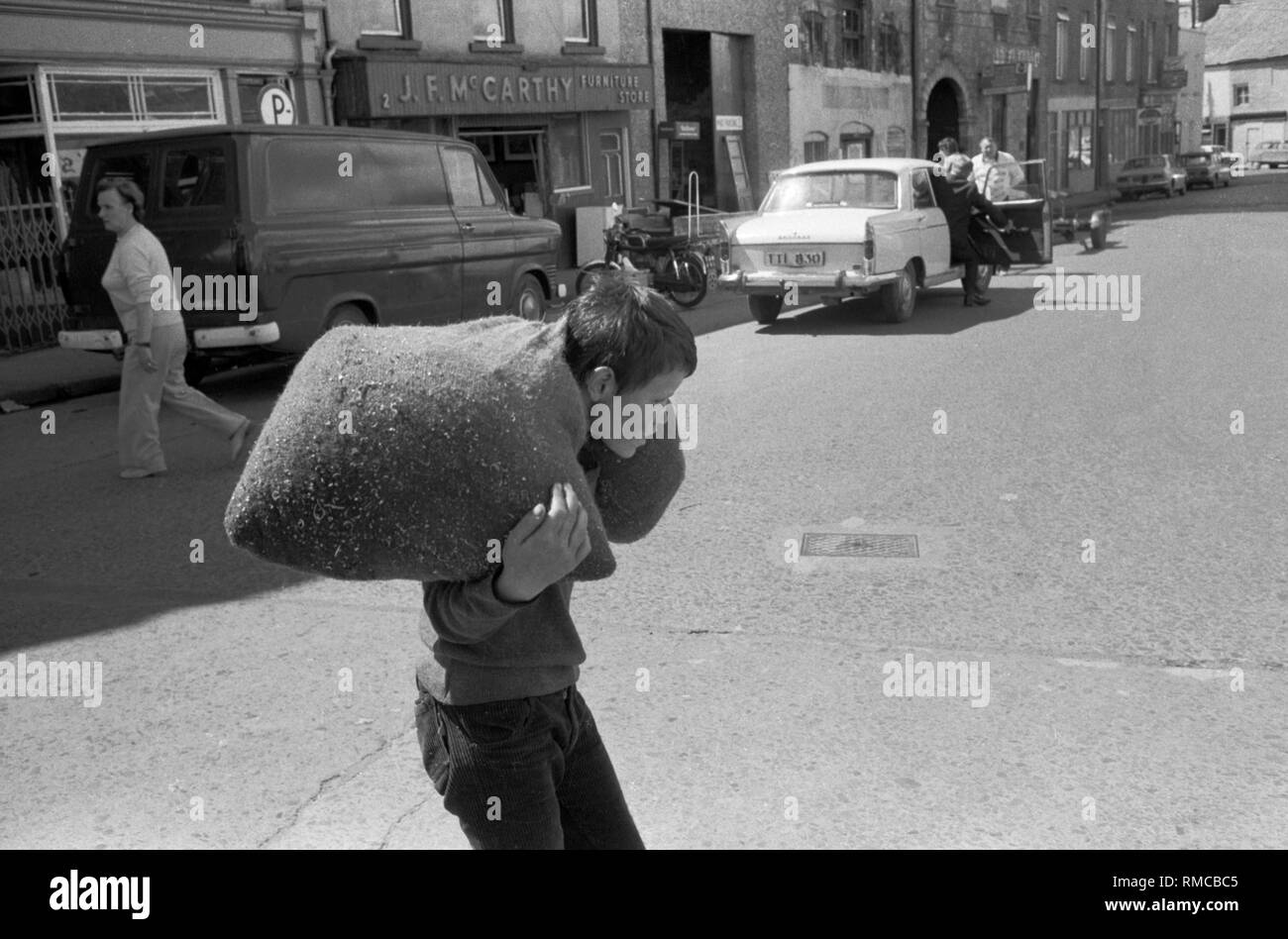 Teenage boy carrying heavy load of metal clippings off cuts taking to a scrap metal dealer. He is working for a living 1970s Irish teen Limerick, in County Limerick, Eire.  West Coast of Southern Ireland 70s HOMER SYKES - Stock Image