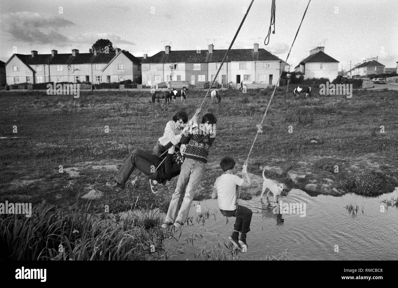 1970s Irish teens playing out side, swinging on ropes having fun together. Friendship.  Limerick, in County Limerick, Eire.  West Coast of Southern Ireland 70s The newly built  South Hill estate. HOMER SYKES - Stock Image