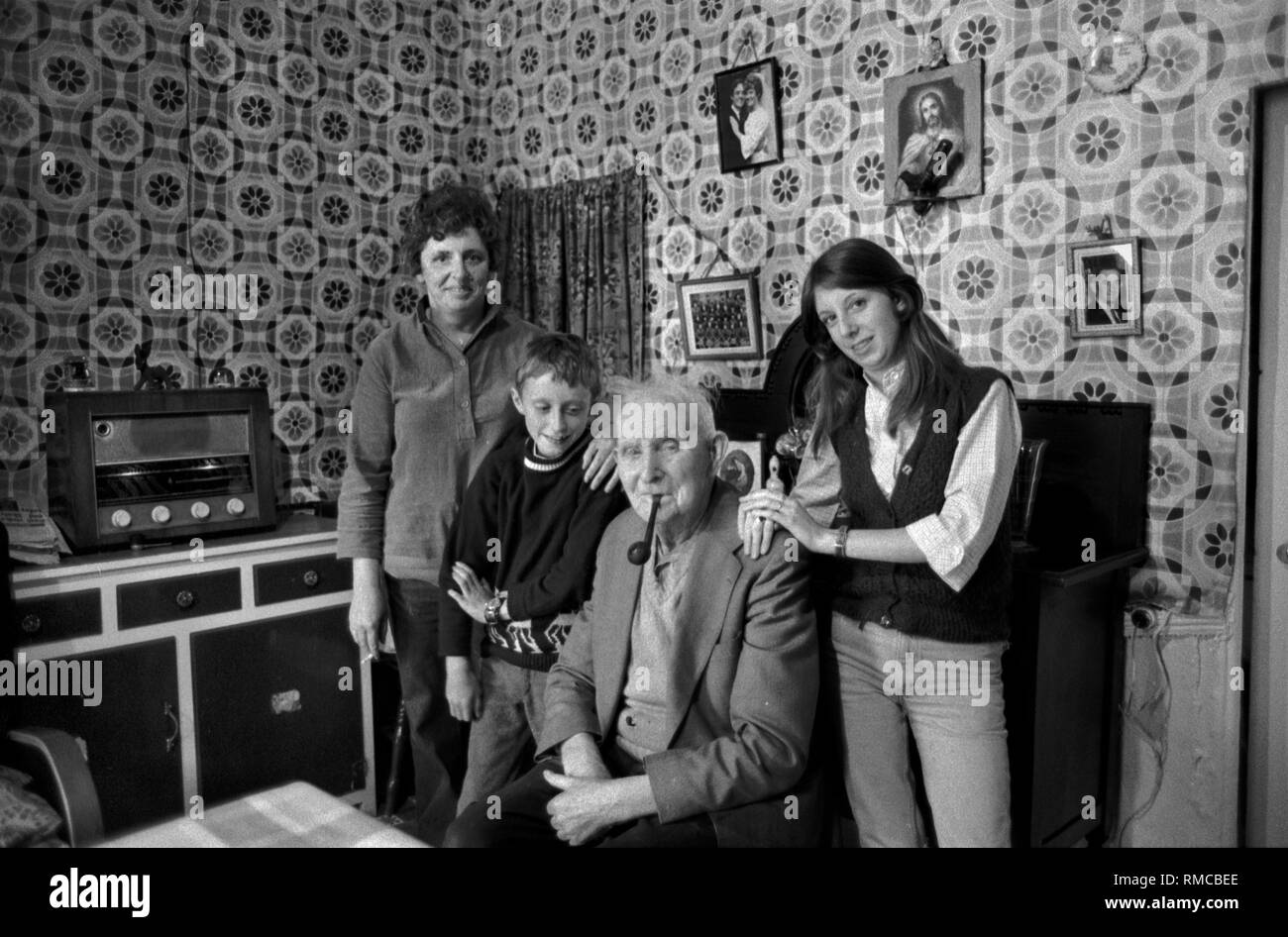 1970s Irish family portrait of three generations interior of family home. Limerick, in County Limerick Eire.  West Coast of Southern Ireland 70s Storan family, Brennans Row Limerick. Joe is 80yrs old and lived here in this two roomed cottage all is life, there is no hot water.  HOMER SYKES - Stock Image