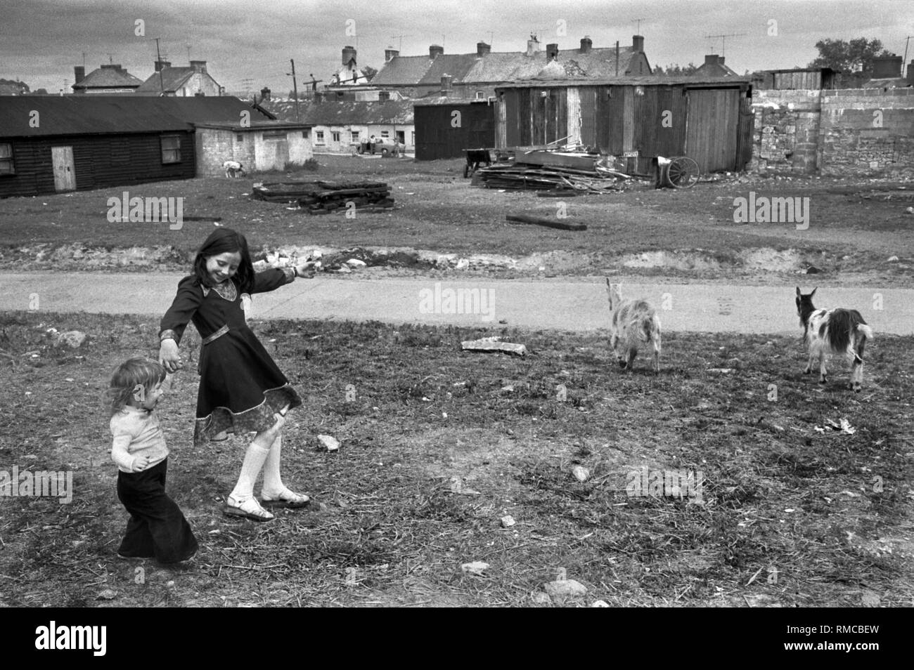 1970s Irish teenage girl with sister playing outside Limerick, in County Limerick, Eire.  West Coast of Southern Ireland 70s HOMER SYKES - Stock Image