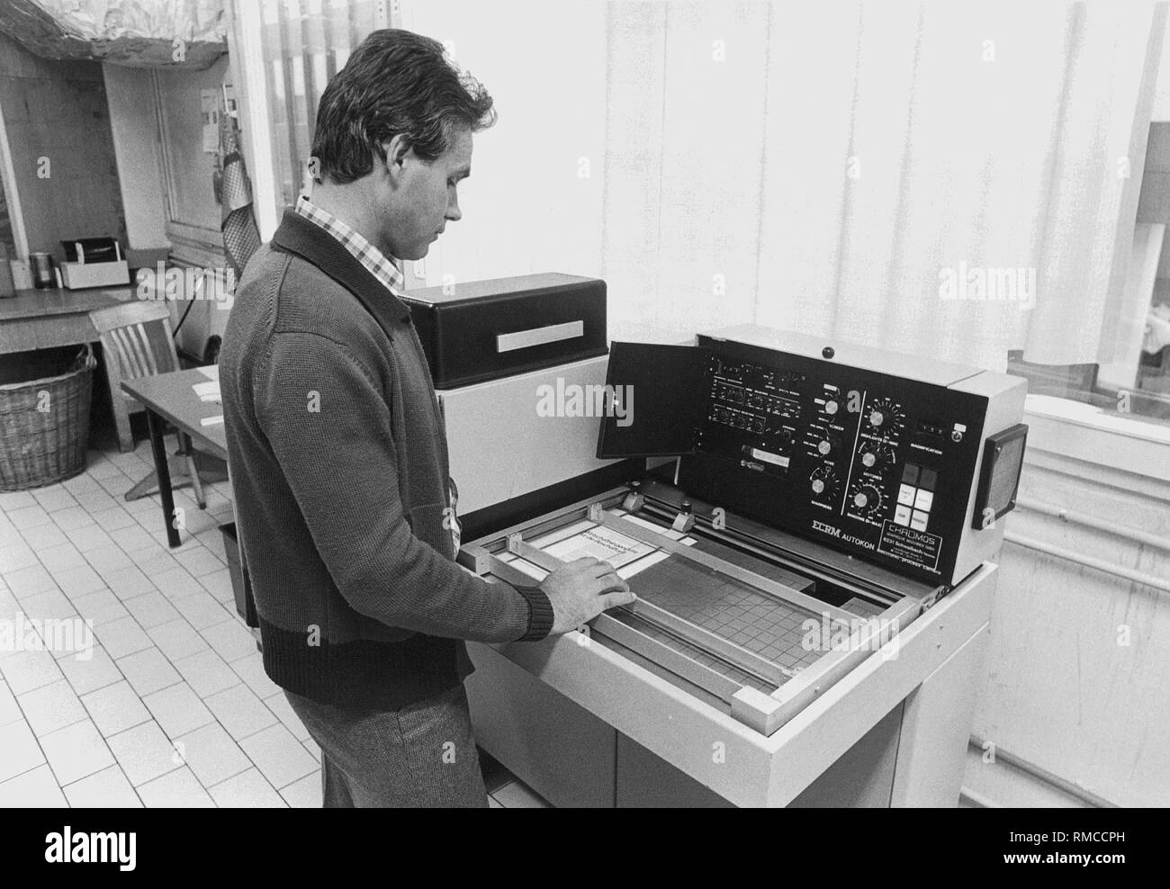 Employees of the repro department at an Autocon scanner. - Stock Image