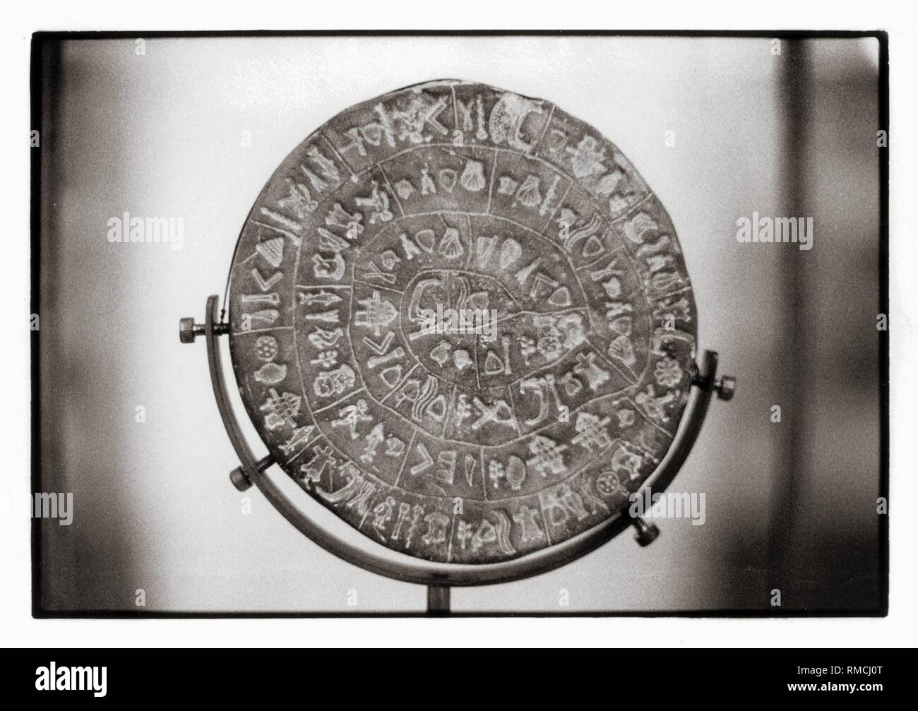 Knossos, Palace of Festos: The world famous Phaistos Disc with hieroglyphic script (around 1700 BC). It was not deciphered until today and is kept in the Museum of Heraklion (modern Greek Iraklion). October 1982. - Stock Image
