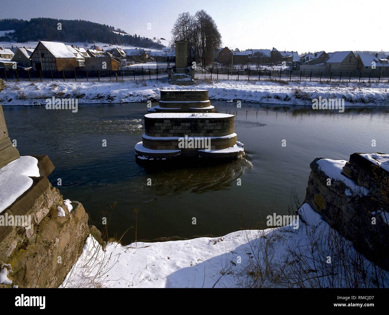 The border between the Federal Republic and the GDR on the Werra at Lauchroeden / GDR: stream barriers, a dismantled bridge and houses behind double steel-lattice fences. - Stock Image