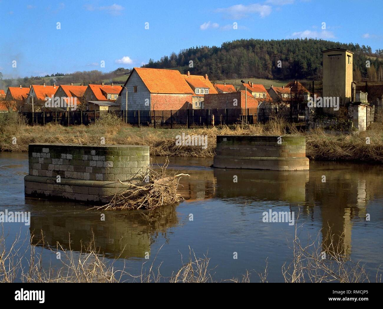 The dismantled bridge on the Werra, beyond the border fence the place Lauchroeden in the GDR. - Stock Image