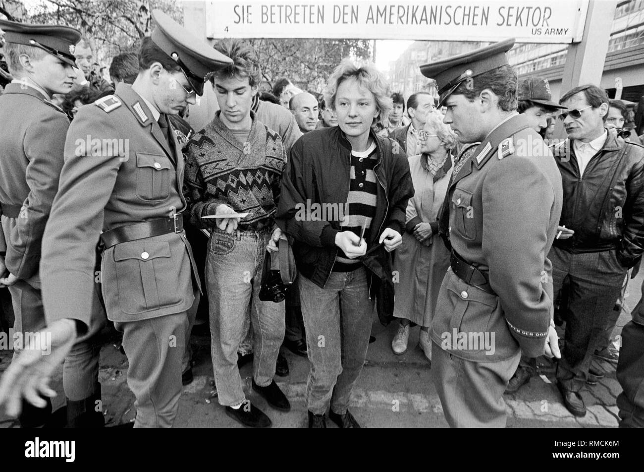 GDR border guards inspect the ID cards of GDR citizens, who return to East Berlin after visiting West Berlin. The picture was taken at the crossing point Checkpoint Charlie in the district of Kreuzberg. - Stock Image