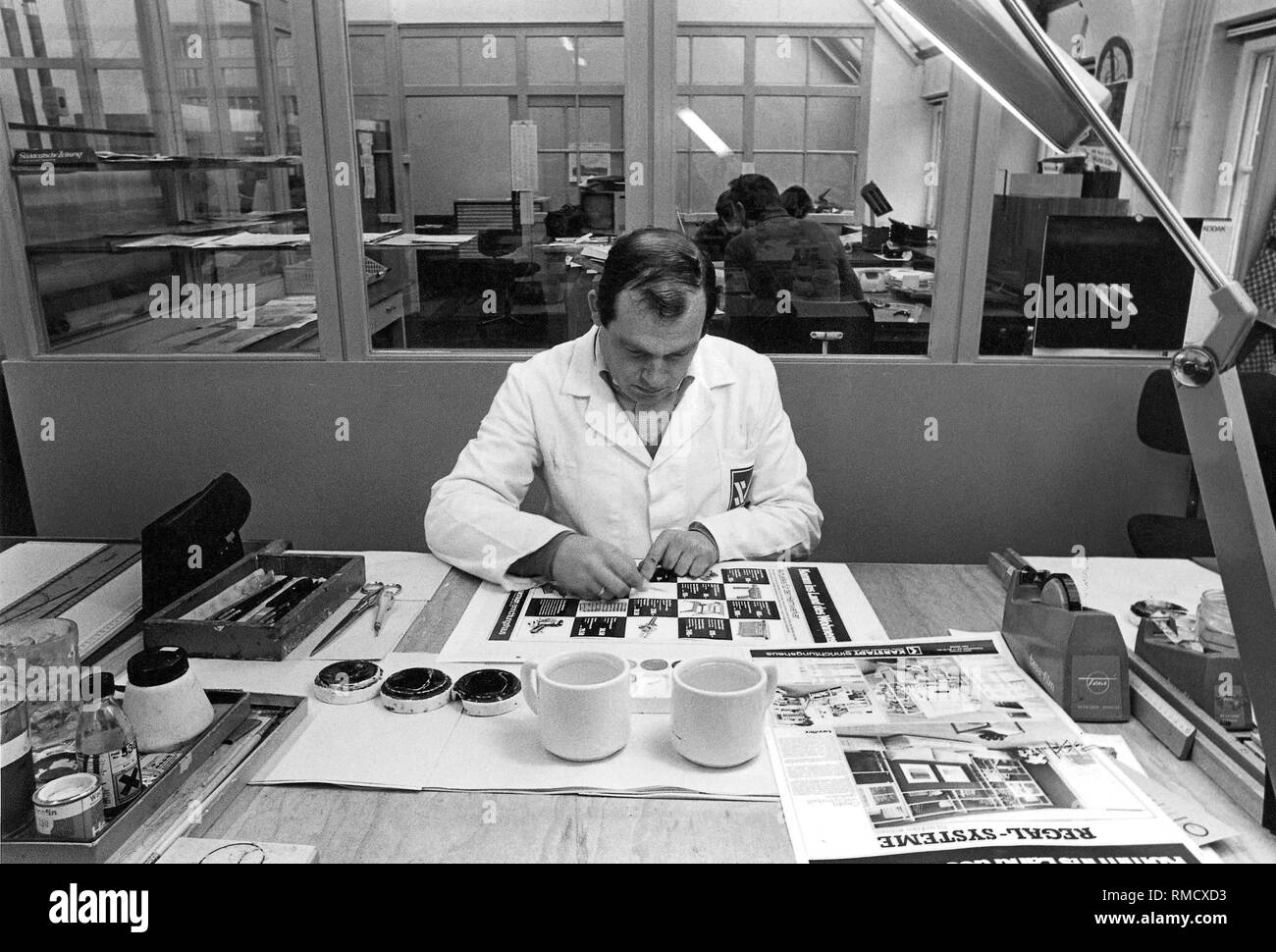 Look into the repro department: man in white coat working on the assembly of a newspaper page. - Stock Image