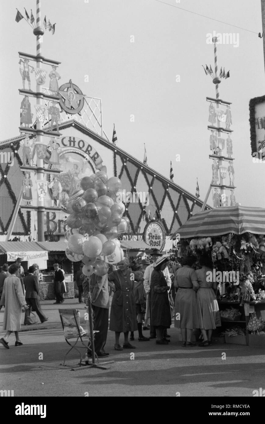 View of a stall at the Munich Oktoberfest. In the background the Festhalle Pschorr Braeurosl and two maypoles. Stock Photo