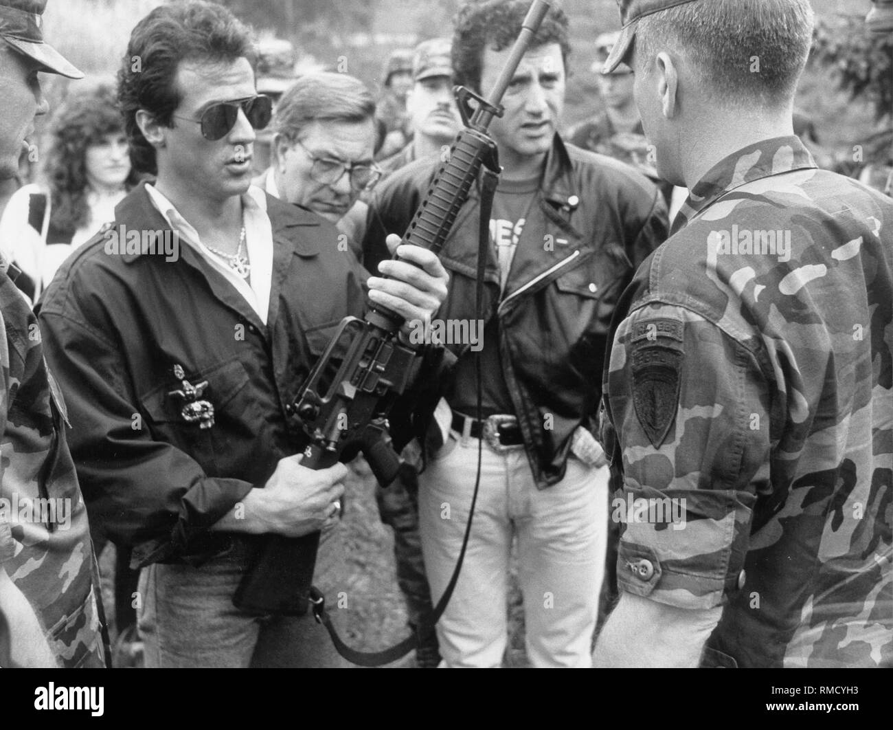 The actor Sylvester Stallone visits American troops in Berlin and here handles an M-16 assault rifle. Right of Sylvester in the background, his brother Frank. - Stock Image