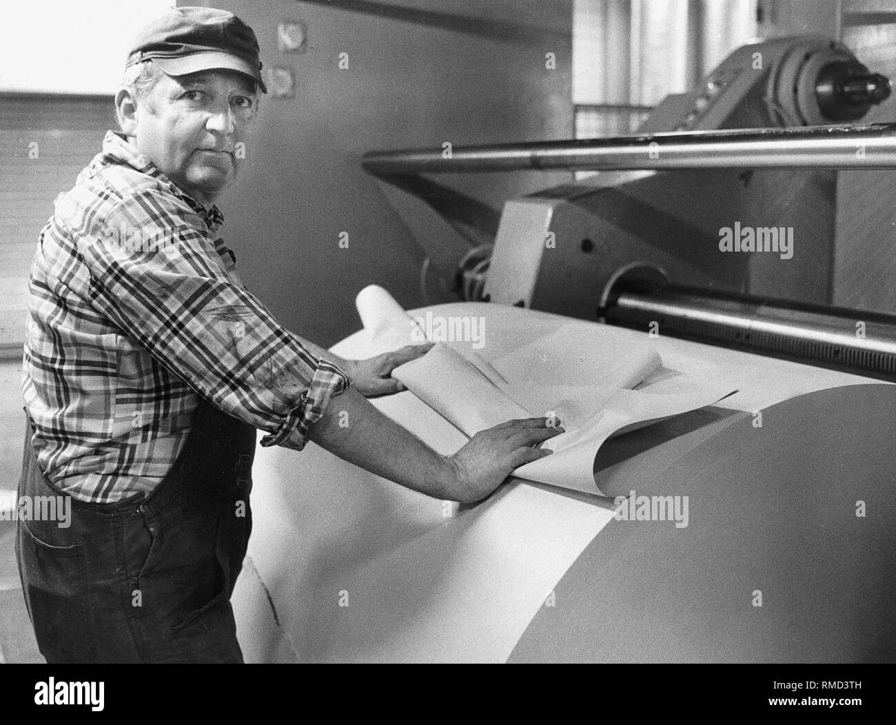 An employee provides for paper supply at a web offset printing press in the printing center of the Sueddeutsche Verlag in Steinhausen. - Stock Image