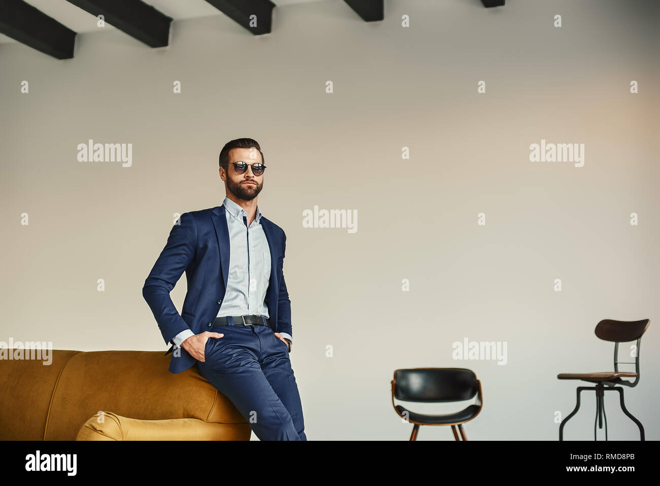 Success in everything... Elegant handsome businessman in stylish suit and dark sunglasses is standing in office and looking away. Bussiness look. Fash - Stock Image