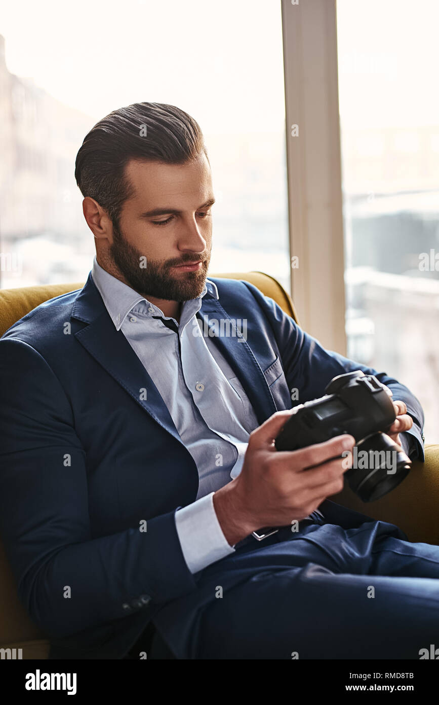 Photography is a Great Hobby...Close-up portrait of young bearded and well dressed businessman who is looking at pictures on camera. Fashion look. Bussiness style - Stock Image