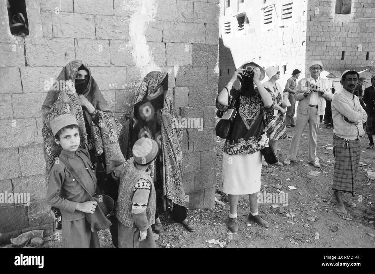 Unrestrained photographing tourists beside veiled women in northern Yemen. - Stock Image
