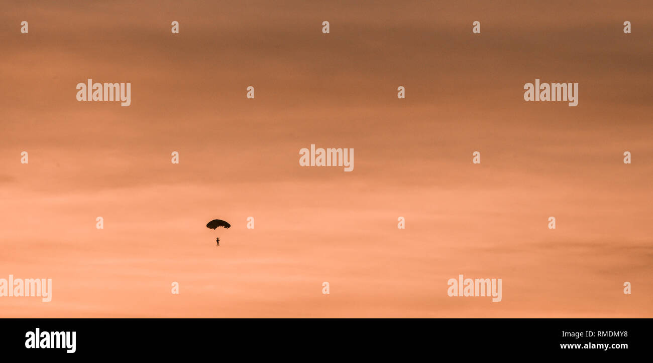 Silhouette of parachutist flying slowly on parachute in the beautiful sky at sunset. - Stock Image