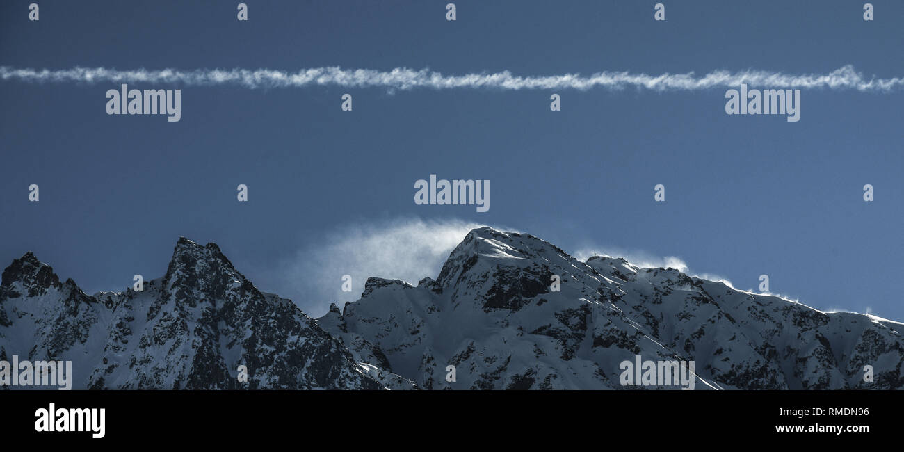 Panoramic blue view of wind blowing over snow capped mountain peaks with plane trail. Copy space for text - Stock Image