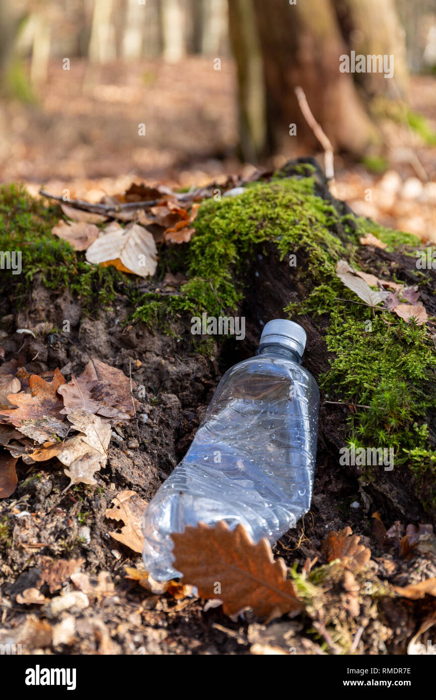 Still life of an empty used plastic bottle waste on forest floor as an environmental pollution closeup - Stock Image