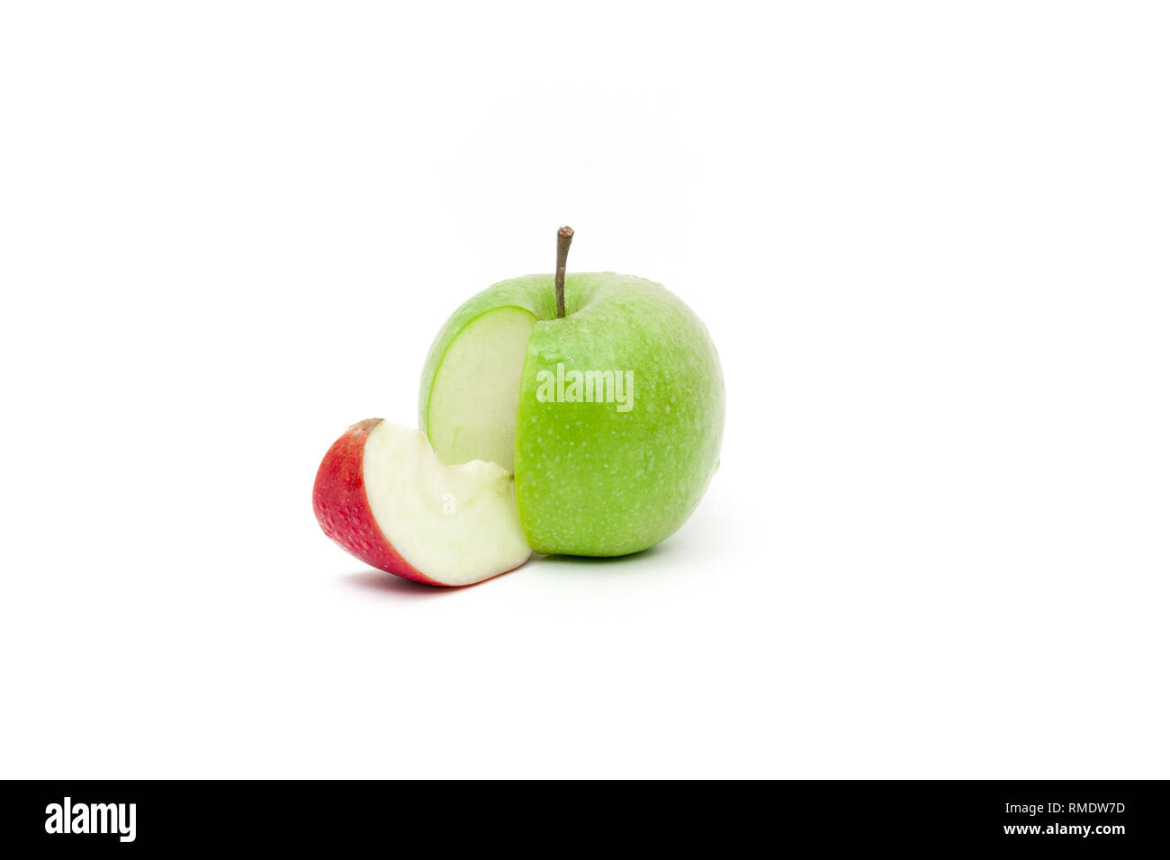 Color complementarity in a juicy green skin apple with a slice of red skin apple - Stock Image