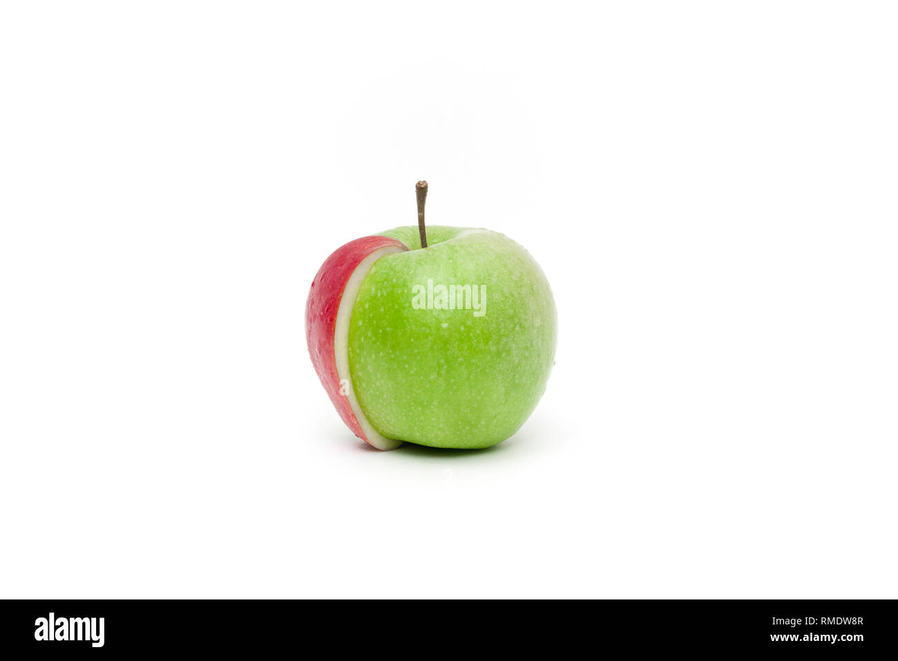 Conceptual view on a green fresh apple with a red slice attached to - Stock Image