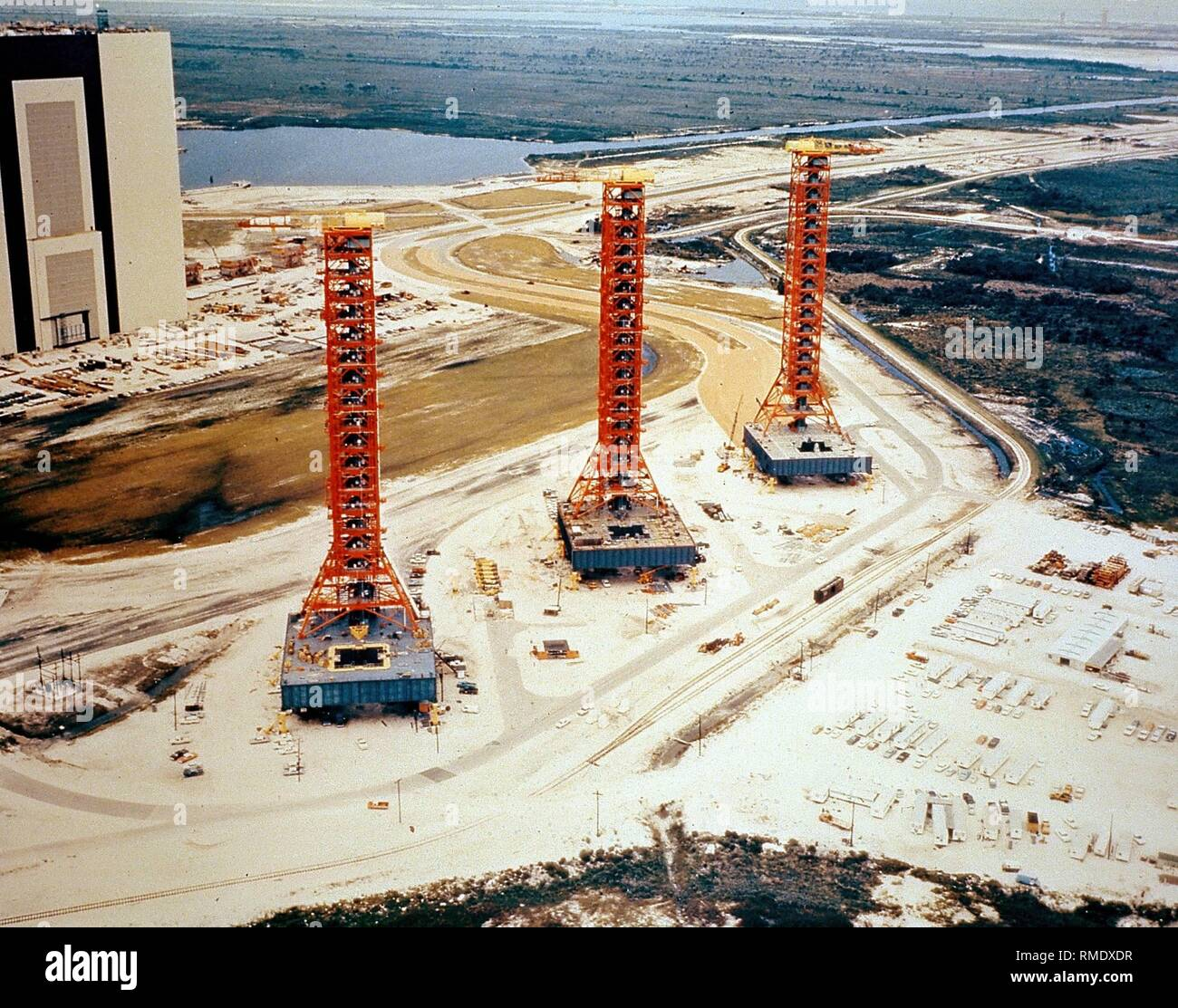 View of the John F. Kennedy Space Center spacecraft launch site with the three mobile rocket launch pads used for the Apollo program. On the left in the background, the Vehicle Assembly Building for spacecrafts. Undated photo, probably from the 1980s. - Stock Image