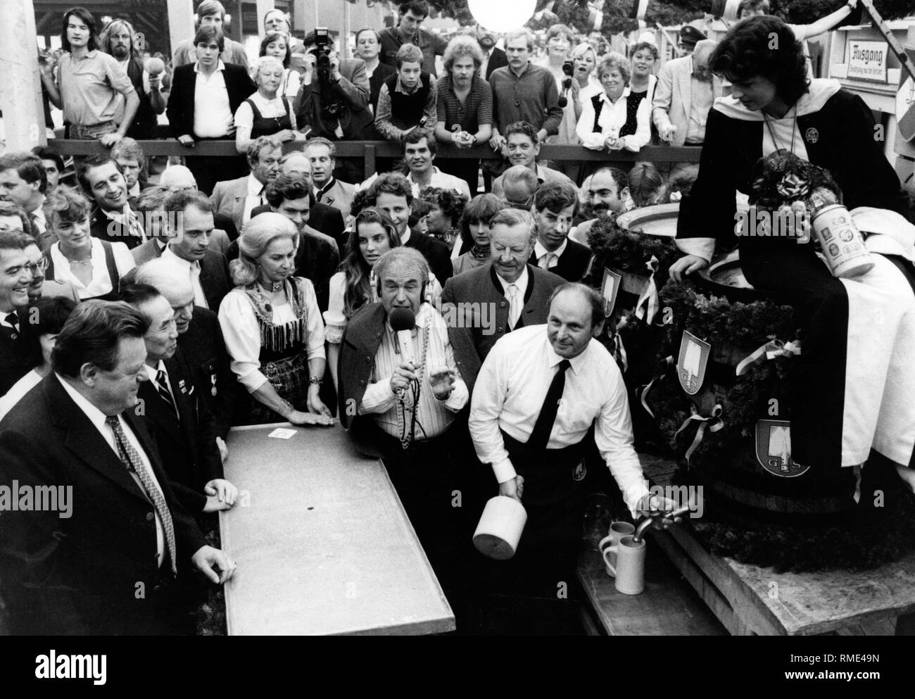 Munich's Lord Mayor Erich Kiesl (CSU, right) opens the Oktoberfest with the traditional tapping of the keg. On the left, the Bavarian Prime Minister Franz-Josef-Strauss. Besides Kiesl, Oktoberfest reporter Michael Stiegler, next to him Edigna Kiesel. In the background at left with microphone, SZ reporter Otto Fischer. - Stock Image