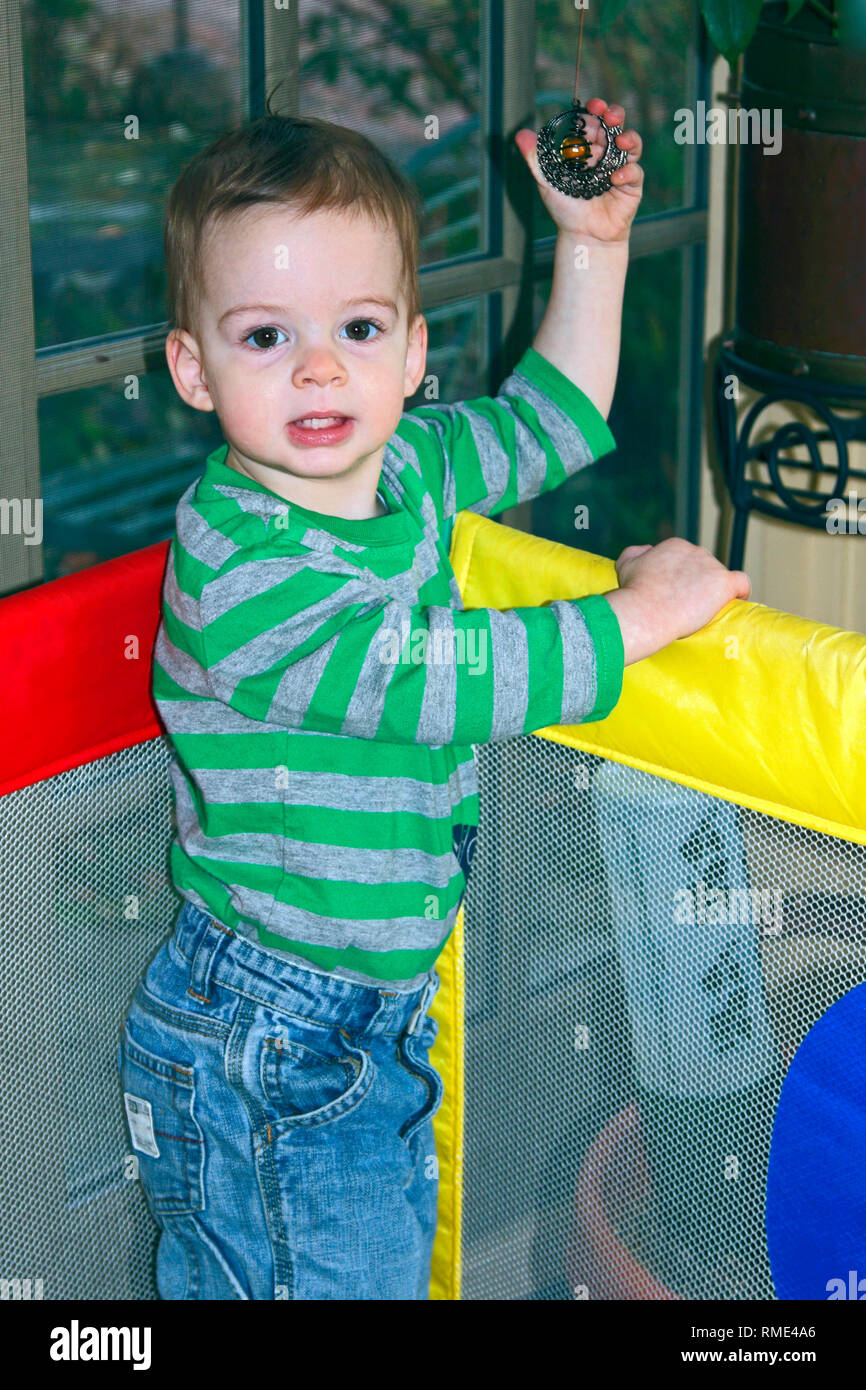 toddler boy standing, colorful mesh playpen; jeans, cute, child, safety, confined, vertical, MR - Stock Image