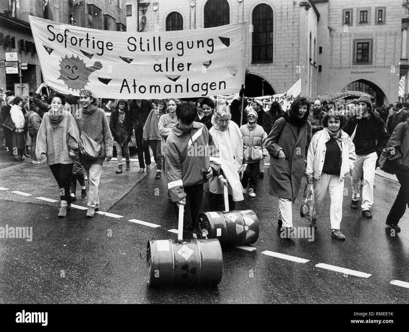 Demonstrators roll 'nuclear waste barrels' over the Marienplatz in Munich. They demonstrate with a banner reading 'Immediate decommissioning of all nuclear facilities' for 'electricity without atom' and against the 'sleaze of the atom mafia'. About 2300 demonstrators took part in the procession. - Stock Image