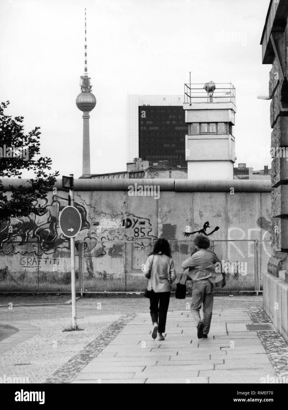 A couple walks towards the Berlin Wall. Behind the Wall, the picture shows a watchtower of the GDR border patrol and the Berlin Television Tower.  Berlin Wall from 1980 until ctober 1989, the, Germany - Stock Image