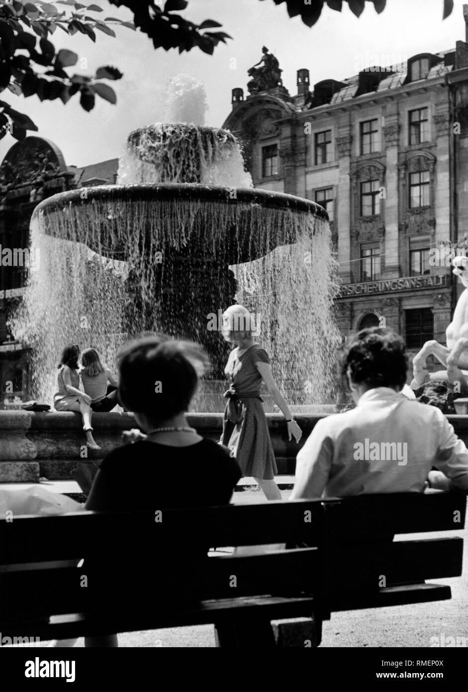 The Wittelsbacher Brunnen (fountain) at the Lenbachplatz in Munich. In front a woman and people on a bench (undated picture). - Stock Image