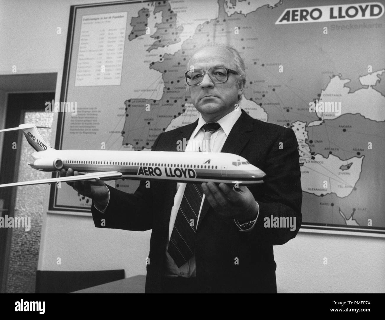 Walter Schneider, managing director of the German airline Aero Lloyd with a model of a McDonnell Douglas MD-83 in front of a route map of his airline. The Aero Lloyd existed from 1980 to 2003, and functioned primarily in the charter business. - Stock Image