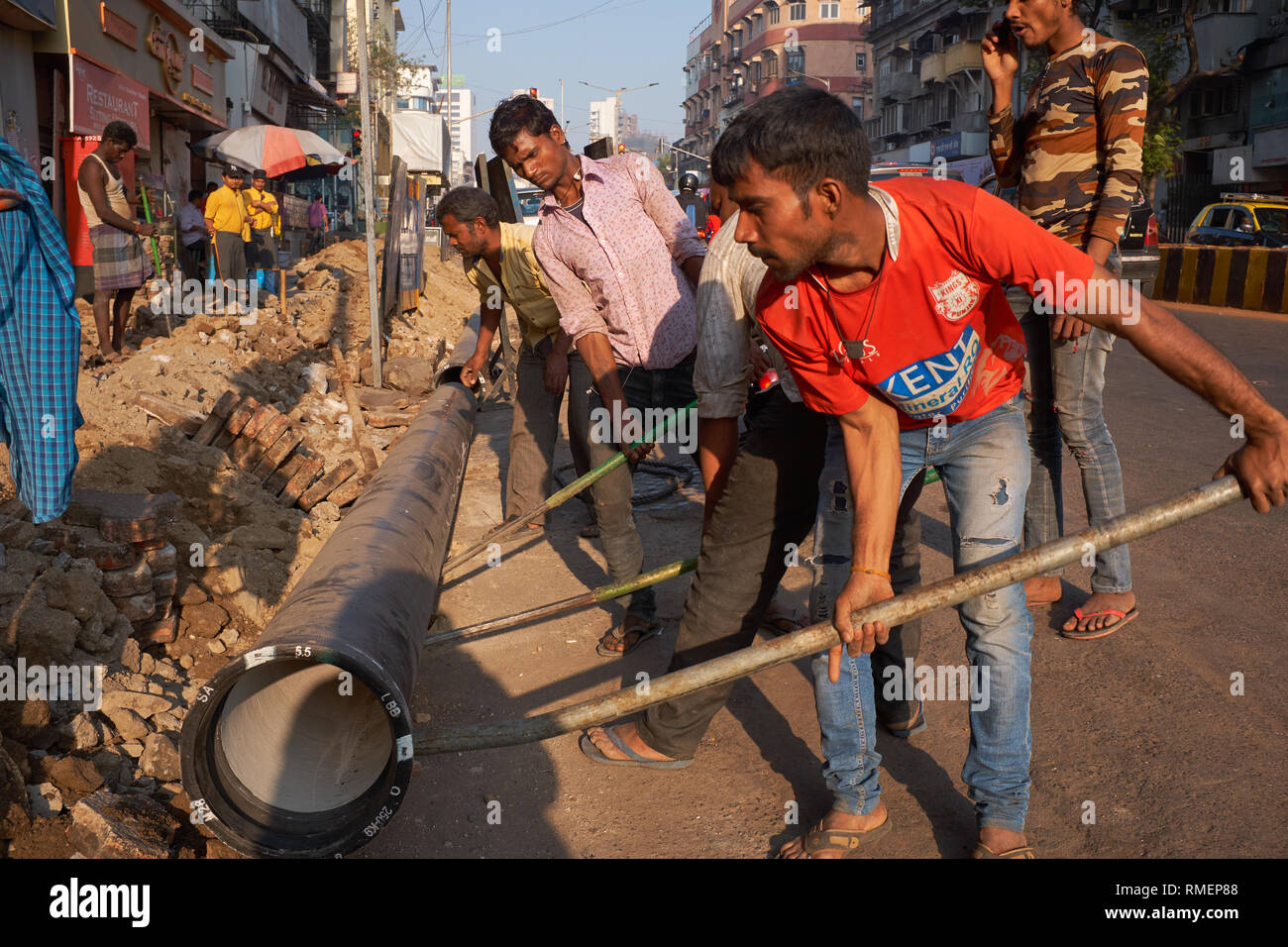 In the wealthy area of Girgaum, near Chowpatty Beach, Mumbai, India, workers use the most basic tools to tear open the footpath & lay new water pipes - Stock Image