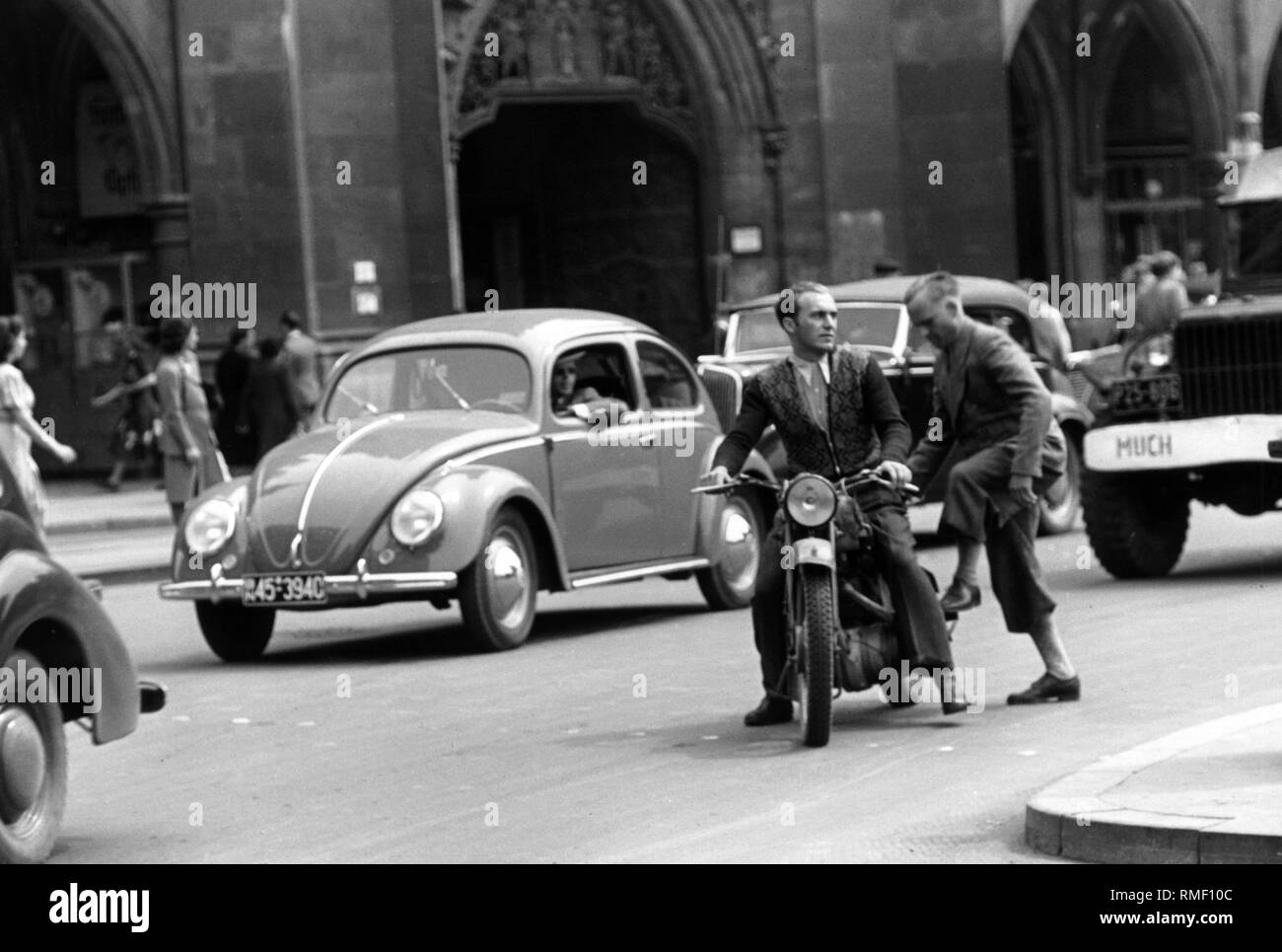 Busy road traffic on the Marienplatz in the Munich city center. The picture shows a VW Beetle, and two men on a motorcycle. - Stock Image