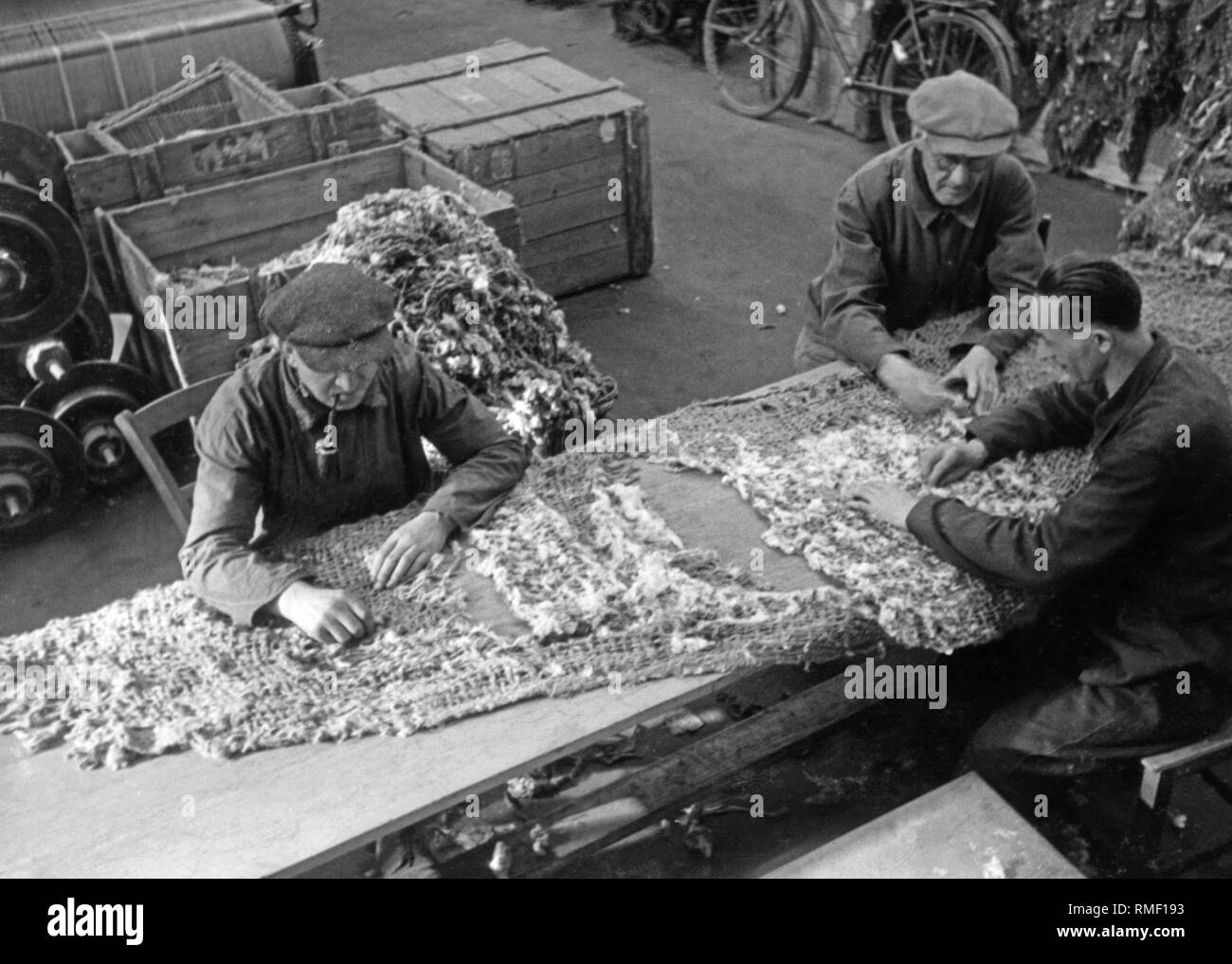 War disabled at their workplace in the cotton mill Baumwollspinnerei am Stadtbach in Augsburg. Jute is plucked and made into carpets. - Stock Image