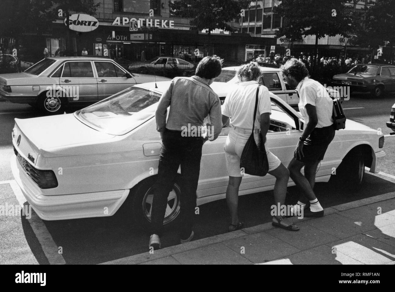 Three passers-by look at a Mercedes 500 SEC (C126 series) with AMG rims and body kit. - Stock Image