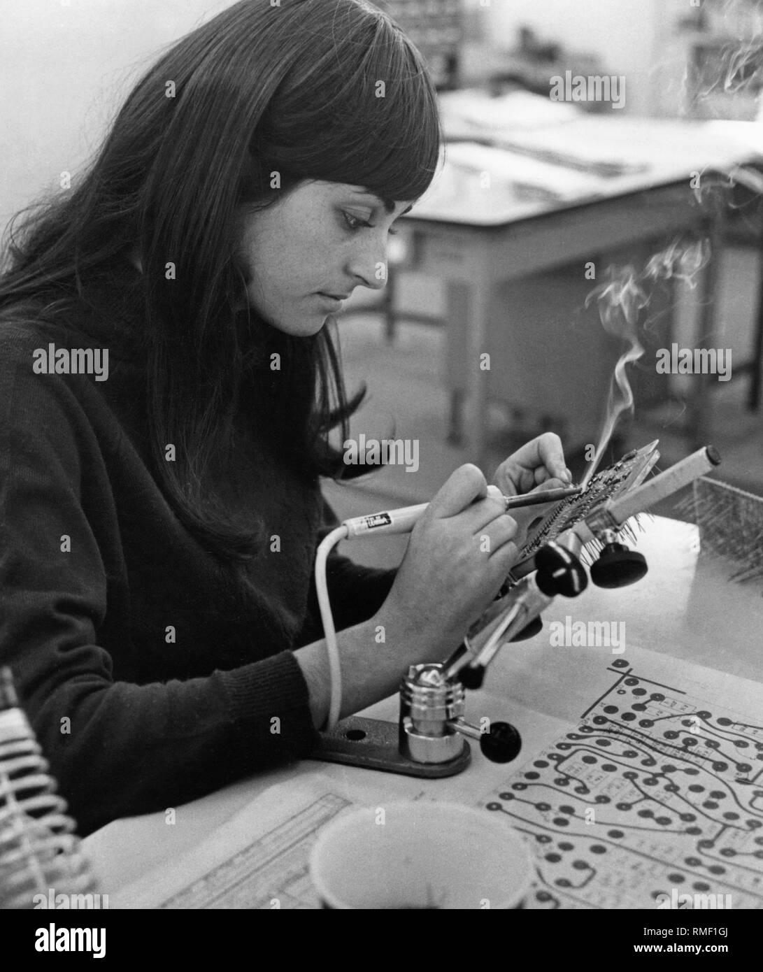 Golan Industries, electronic department: a woman brazes components on a printed circuit board. Golan specialized in the production of catapult seats for military aircrafts. - Stock Image