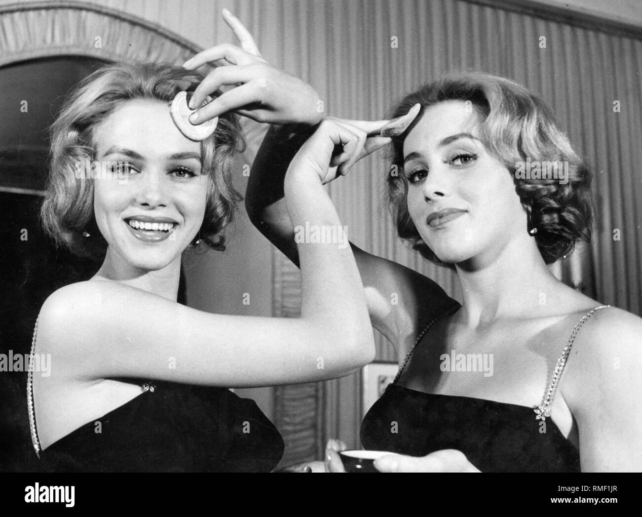 The Kessler twins, Alice and Allen Kessler, put on make-up. - Stock Image