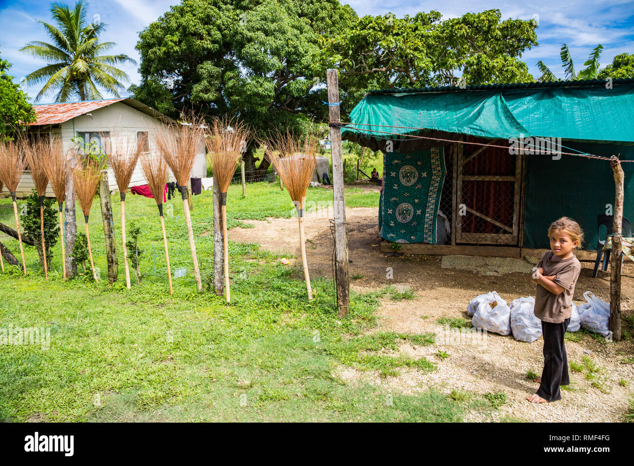 Tongatapu, Tonga - Jan 4 2014: a small local native indigenous Polynesian girl sells hand made brooms and plastic bags with sweet potato kumara. A poo - Stock Image
