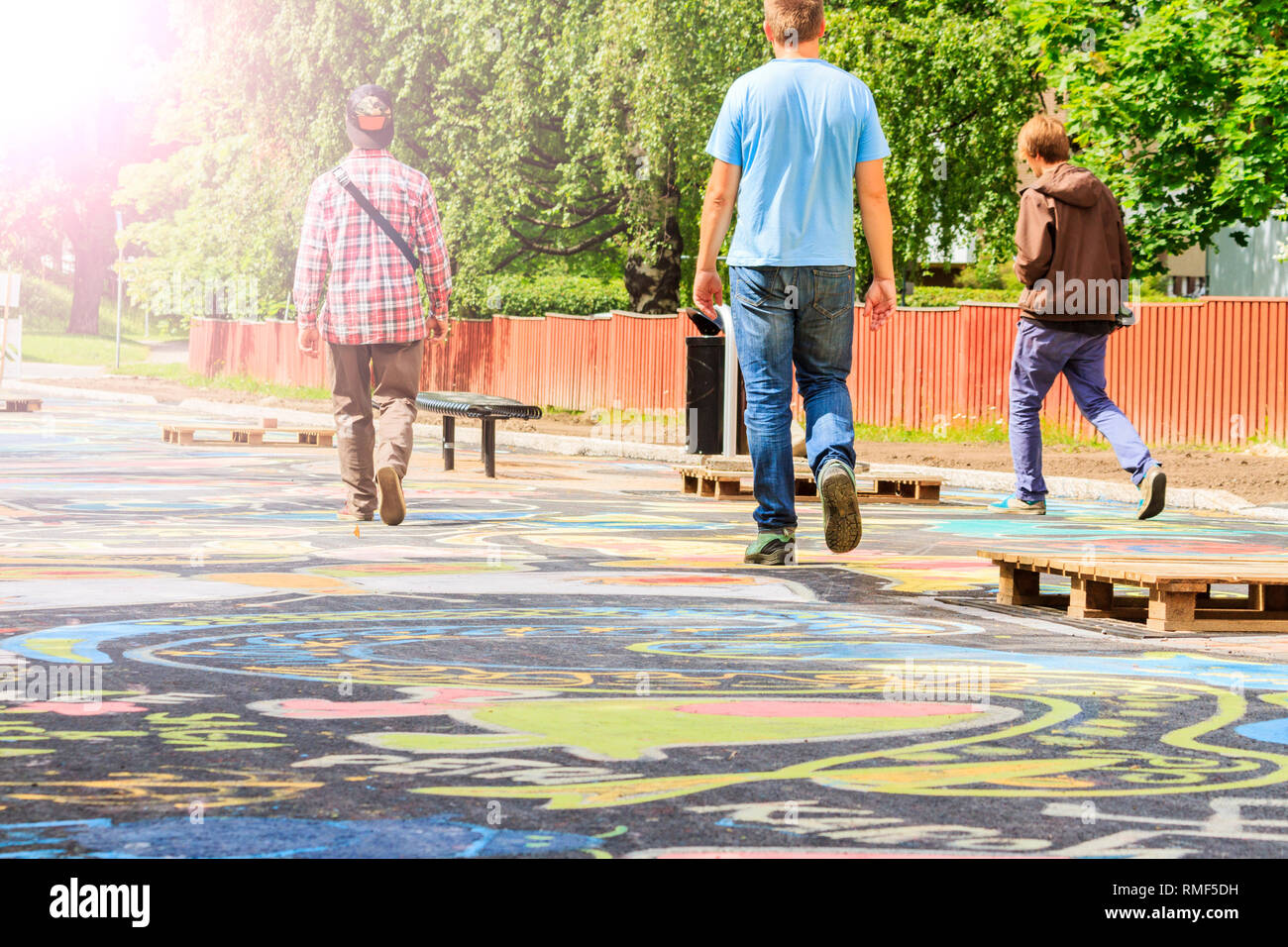 three guys walking in a small street - Stock Image