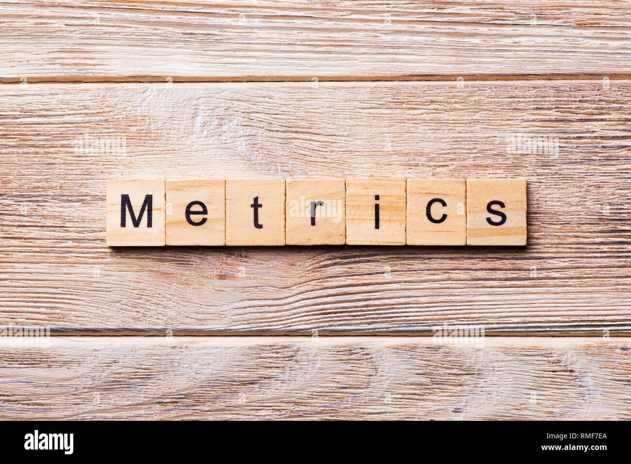 METRICS word written on wood block. METRICS text on wooden table for your desing, concept. - Stock Image