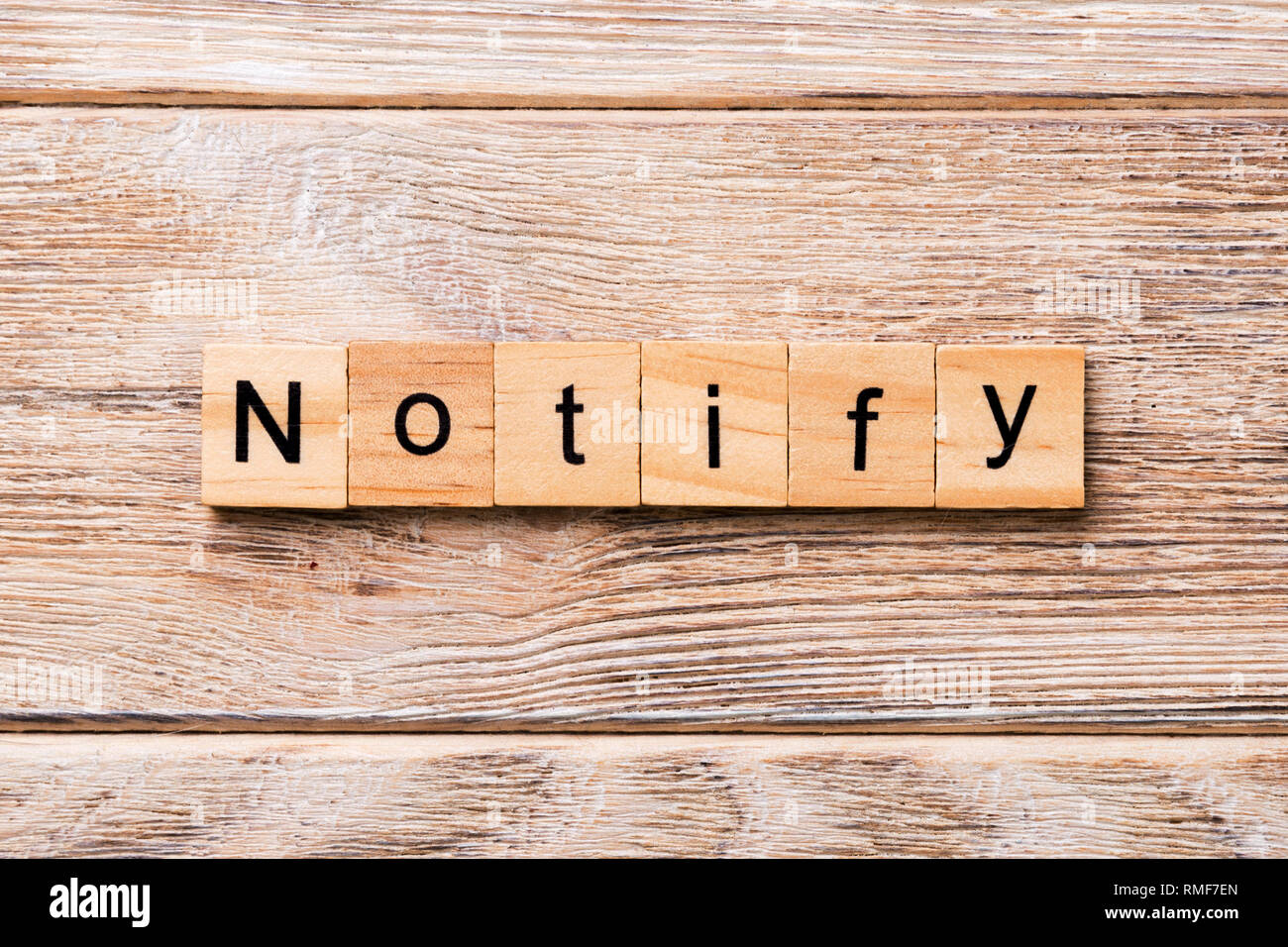 NOTIFY word written on wood block. NOTIFY text on wooden table for your desing, concept. - Stock Image